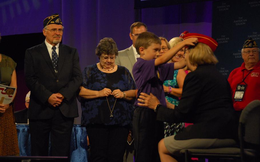 Denise Rohan, right, sits as her grandson, Sawyer, places her new cap on her head onstage during the American Legion National Convention in Reno, Nev. on Thursday, Aug. 24. Rohan was elected to be the group's new national commander.
