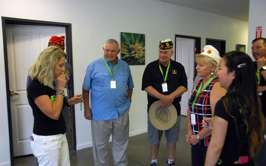 """Alise Dalrymple, left, takes a typical """"dose"""" of marijuana from a vaporizer pen at Nevada Botanical Science in Reno, Nev. on Wednesday, Aug. 23. American Legion members Wayne Stacey, Ron Bradstreet and Donna Stacey, watch."""
