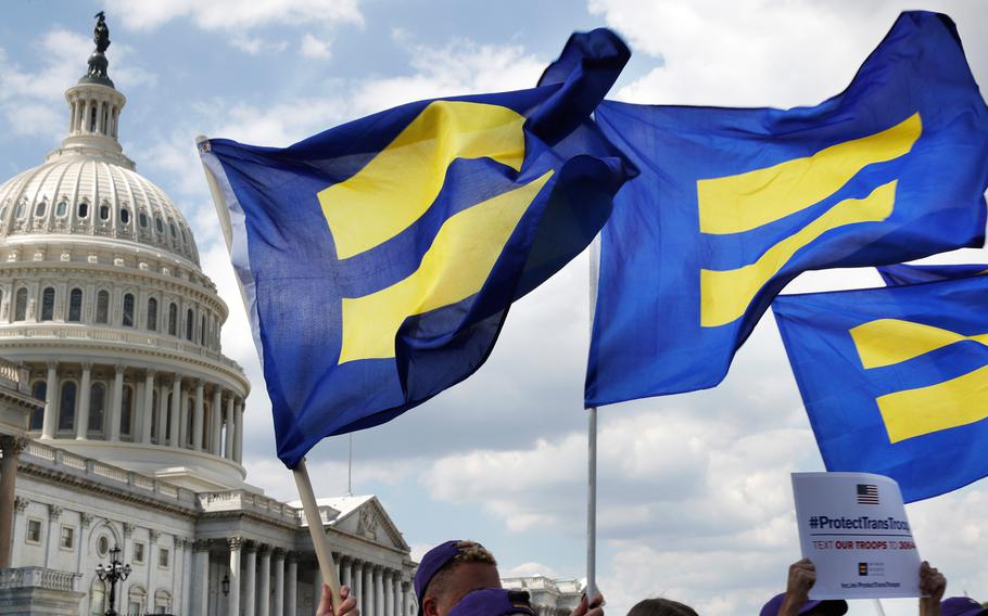 """In this July 26, 2017 file photo, people with the Human Rights Campaign hold up """"equality flags"""" during an event on Capitol Hill in Washington, in support of transgender members of the military."""
