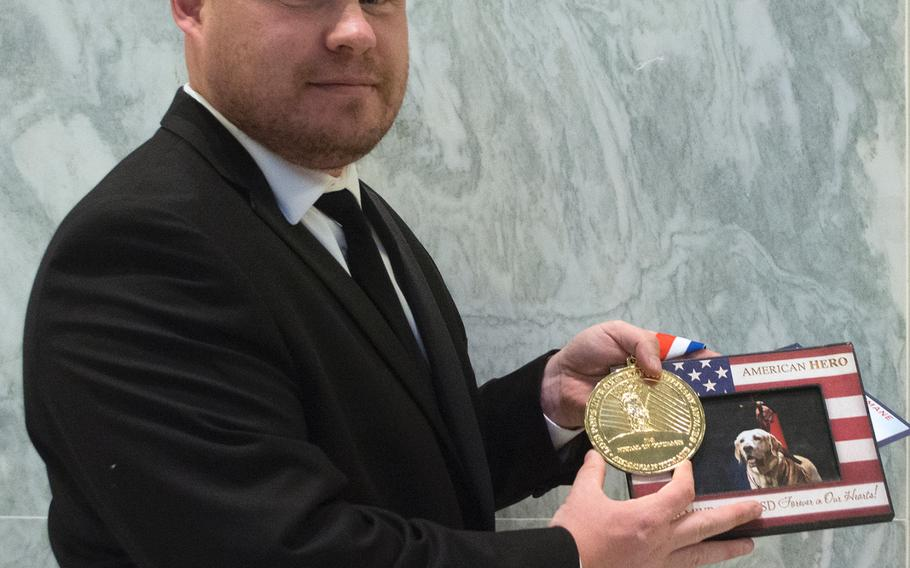 Army Sgt. 1 st Class Chuck Shuck shows of Gabe's medal and photo at the American Humane's K-9 Medal of Courage Awards on Capitol Hill on Oct. 11, 2017. Gabe was being honored in memoriam.