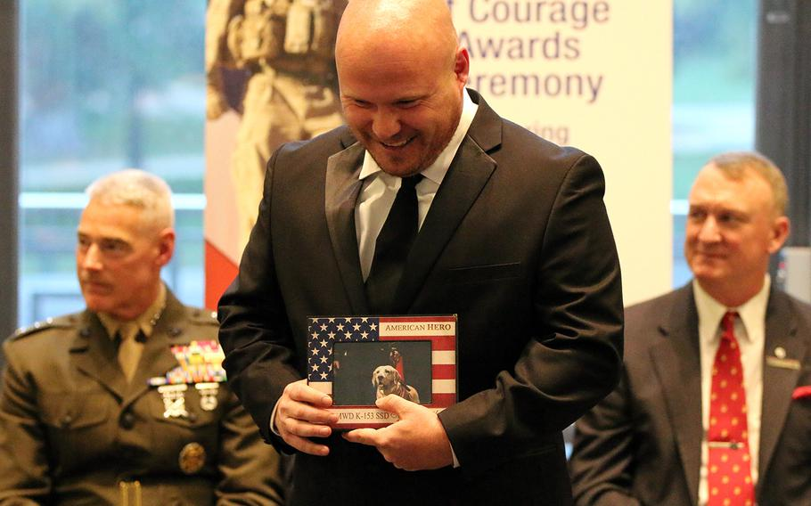Army Sgt. 1 st Class Chuck Shuck holds a picture of military working dog Gabe at the American Humane's K-9 Medal of Courage Awards on Capitol Hill on Oct. 11, 2017. Gabe was receiving his medal in memoriam.