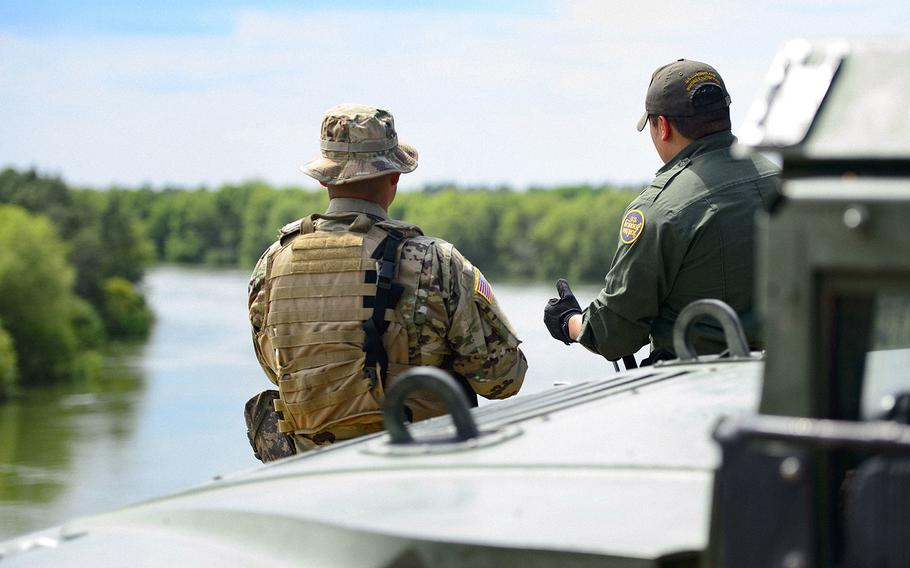 A Texas Guardsman and a Customs and Border Patrol agent stand near the shores of the Rio Grande River in Starr County, Texas as part of the federal call-up to the Texas Mexico border in April 2018.