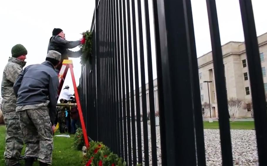 A video screen grab shows volunteers placing wreaths on a fence at the Pentagon's 9/11 memorial during a Wreaths Across America ceremony, Dec. 15, 2017.