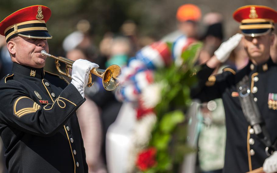 An Army bugler plays taps to conclude a special wreath-laying ceremony at Arlington National Cemetery's Tomb of the Unknowns on Friday, March 23, 2018.