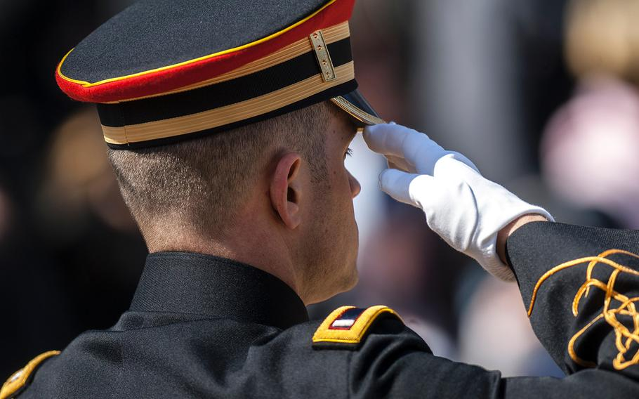 An Army band member salutes during the playing of taps to conclude a special wreath-laying ceremony at Arlington National Cemetery's Tomb of the Unknowns on Friday, March 23, 2018.