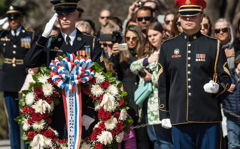 Members of a ceremonial honor guard salute and stand at attention before the start of a wreath-laying ceremony at Arlington National Cemetery's Tomb of the Unknowns on Friday, March 23, 2018.