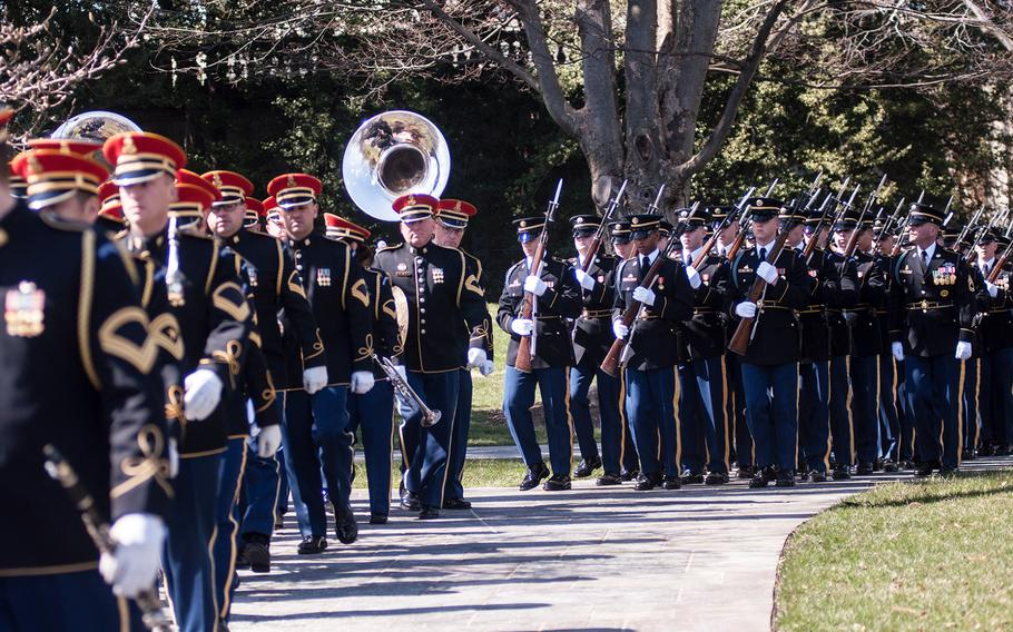 """Members of the United States Army Band, """"Pershing's Own,"""" and a ceremonial unit of soldiers march away from Arlington National Cemetery's Tomb of the Unknowns on Friday, March 23, 2018, following a special wreath-laying ceremony."""