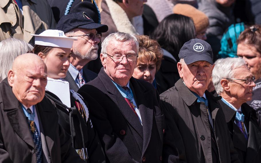 A crowd of onlookers, including more than two dozen Medal of Honor recipients, watch an Army sentry perform his guard duties before the start of a special wreath-laying ceremony at Arlington National Cemetery's Tomb of the Unknowns on Friday, March 23, 2018.
