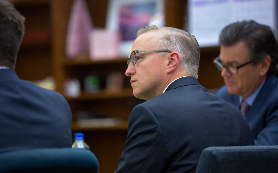 Navy Cmdr. John Michael Neuhart II, center, and his defense lawyer Kerry Armstrong listen as the prosecution questions a witness on the stand in this file image from Nov. 2017.