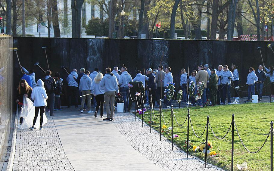 Employees of NewDay USA and the New Day USA Foundation scrub the iconic wall at the Vietnam Veterans Memorial on Saturday, April 21, 2018.