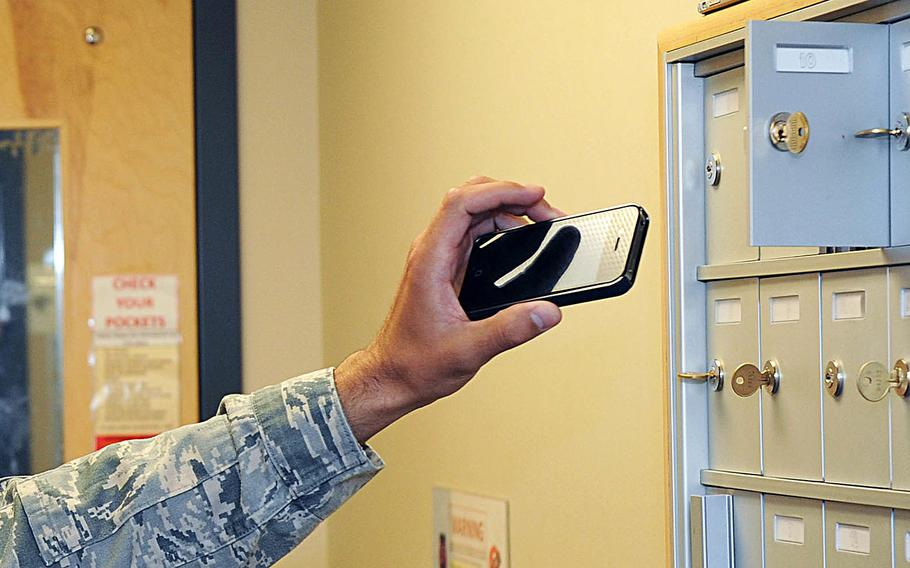 An airman puts his smartphone in a locker before entering the intelligence room at McConnell Air Force Base in Kansas on May 12, 2015.