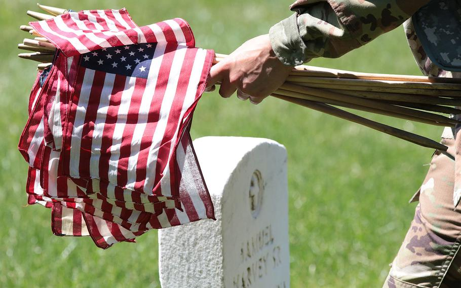Soldiers with the 3d U.S. Infantry Regiment (The Old Guard) placed flags in front of headstones at Arlington National Cemetery on Thursday, May 24, 2018 during the annual pre-Memorial Day Flags-In ceremony.