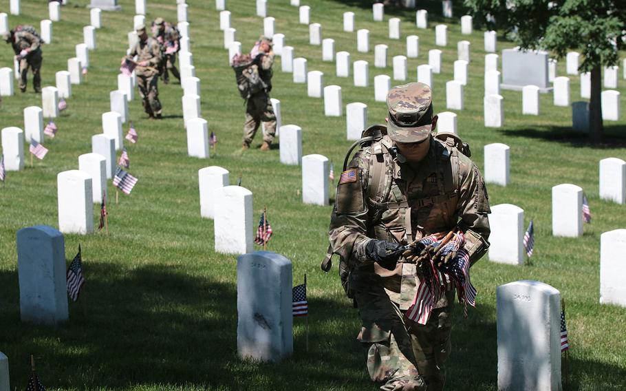 Soldiers with the 3d U.S. Infantry Regiment (The Old Guard) place flags in front of headstones at Arlington National Cemetery on Thursday, May 24, 2018. The annual pre-Memorial Day Flags-In ceremony has taken place every year since The Old Guard was designated as the U.S. Army's official ceremonial unit in 1948.