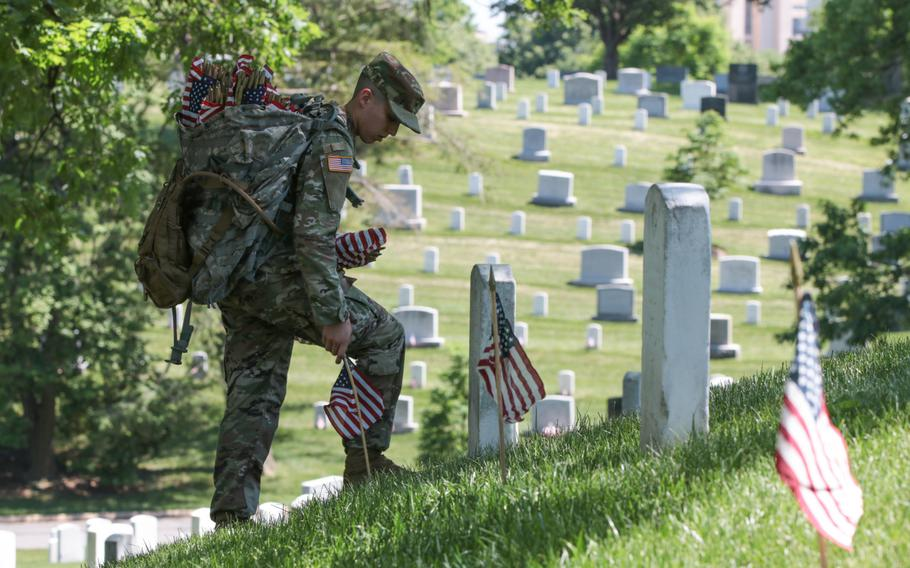 A soldier with the U.S. Army's 3rd Infantry Regiment places a flag at a grave at Arlington National Cemetery as The Old Guard visited graves throughout the cemetery for Flags In on May 24, 2018.