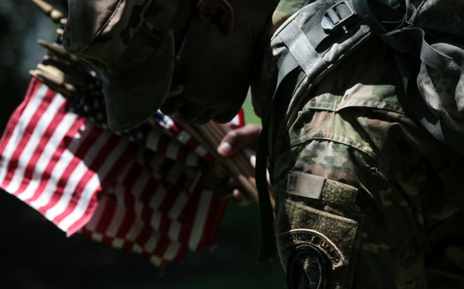 A soldier with the U.S. Army's 3rd Infantry Regiment, better known as The Old Guard, places a flag at a grave at Arlington National Cemetery as The Old Guard visited graves throughout the cemetery for Flags In on May 24, 2018.