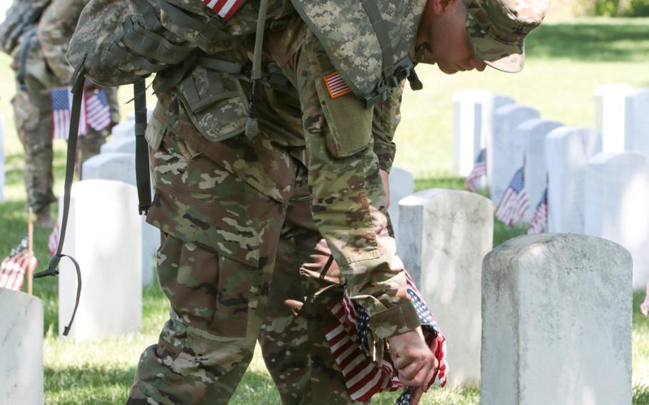 A soldier with the U.S. Army's 3rd Infantry Regiment, better known as The Old Guard, places a flag at a gravesite at Arlington National Cemetery as The Old Guard visited graves throughout the cemetery for Flags In on May 24, 2018.