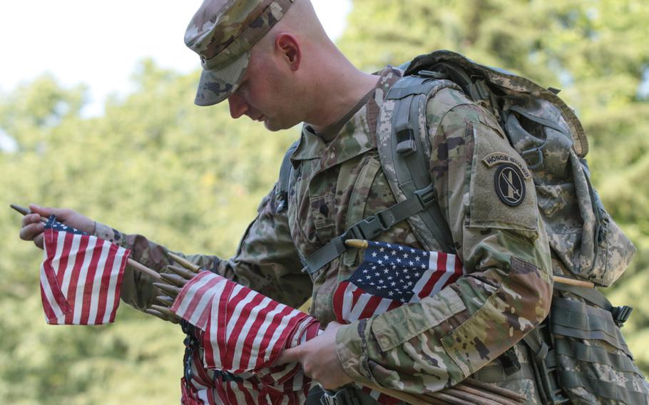 Spc. Richard Broseman, 32, selects a flag to place at a gravesite at Arlington National Cemetery at Flags In on May 24, 2018.
