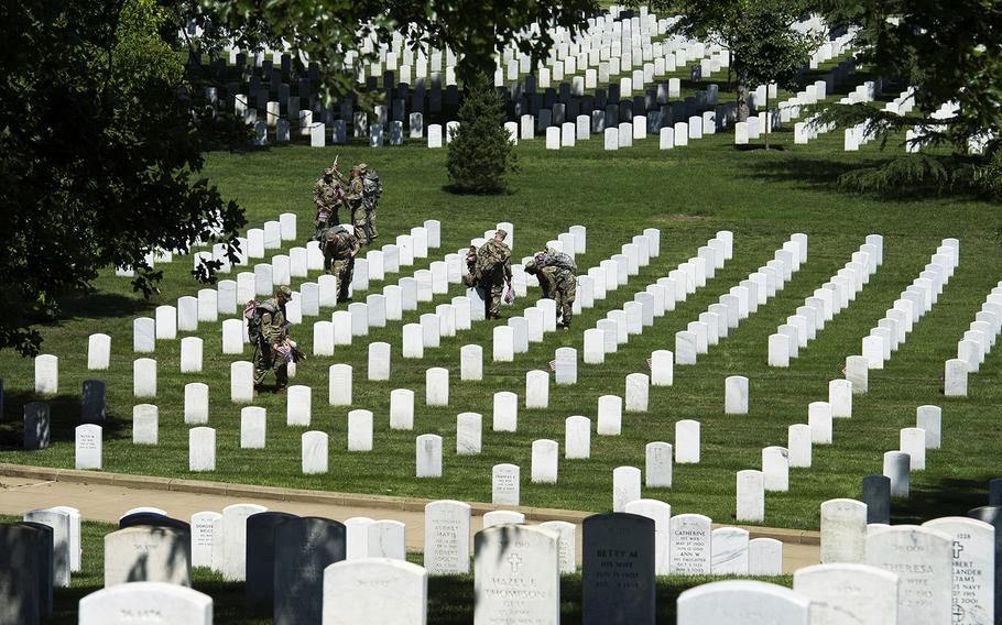 Members of the Army 3d U.S. Infantry Regiment, The Old Guard, place flags at the headstones of fallen military members during its annual Flags In ceremony at Arlington National Cemetery on May 24, 2018, in Arlington, Va.