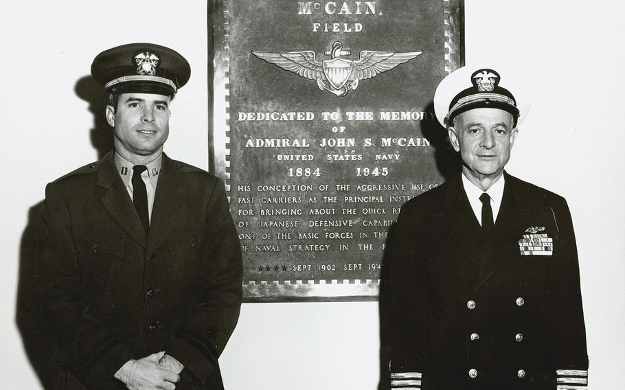 John McCain III, left, standing with his father, Adm. John S. McCain Jr., right, in front of a plaque dedicated to McCain's grandfather Adm. John McCain Sr.