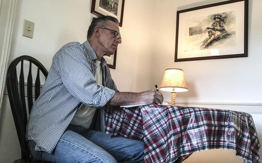 Gettysburg Artist-in-Residence Rick Stark Jr. goes over his notes for a recently-written poem.