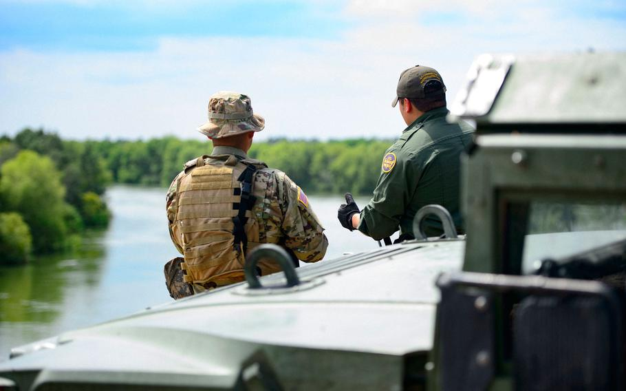 A Texas Guardsmen and a Customs and Border Patrol agent discuss the lay of the land on the shores of the Rio Grande River in Starr County, Texas in April as part of the federal call-up to the Texas Mexico border.