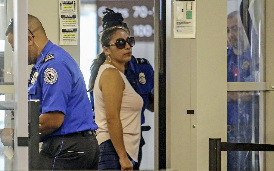 Alejandra Juarez, 38, center, passes through TSA screening at the Orlando International Airport on Friday, Aug. 3, 2018 in Orlando, Fla.  Juarez, the wife of a former Marine is preparing to self-deport to Mexico in a move that would split up their family.