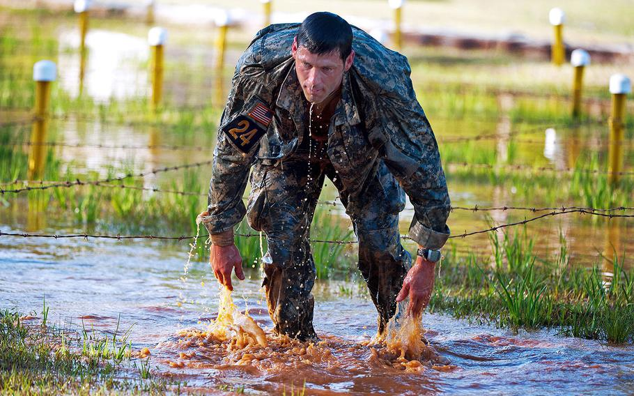 """Master Sgt. Christopher Nelms, U.S. Special Operations Command, finishes a low craw under the """"worm pit"""" at the Malvesti Obstacle Course in the Best Ranger Competition on April 13, 2013 at Fort Benning."""