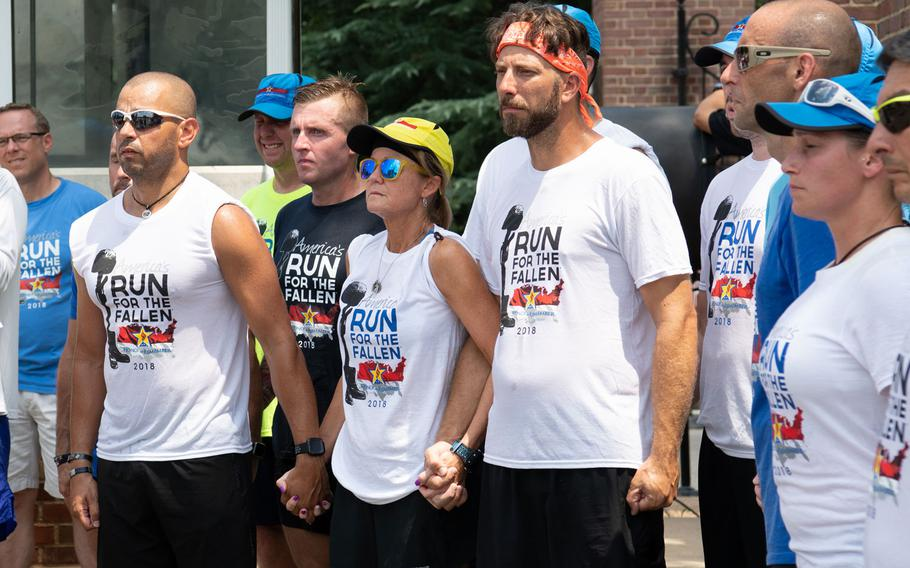 The runners of the final leg of the Run for the Fallen support each other during a ceremony at which the names of deceased servicemembers were read, at Arlington National Cemetery on Aug. 5, 2018. The Run for the Fallen traversed 19 states over five months, over a route that covered almost 6,000 miles. Each mile honored deceased American servicemembers.