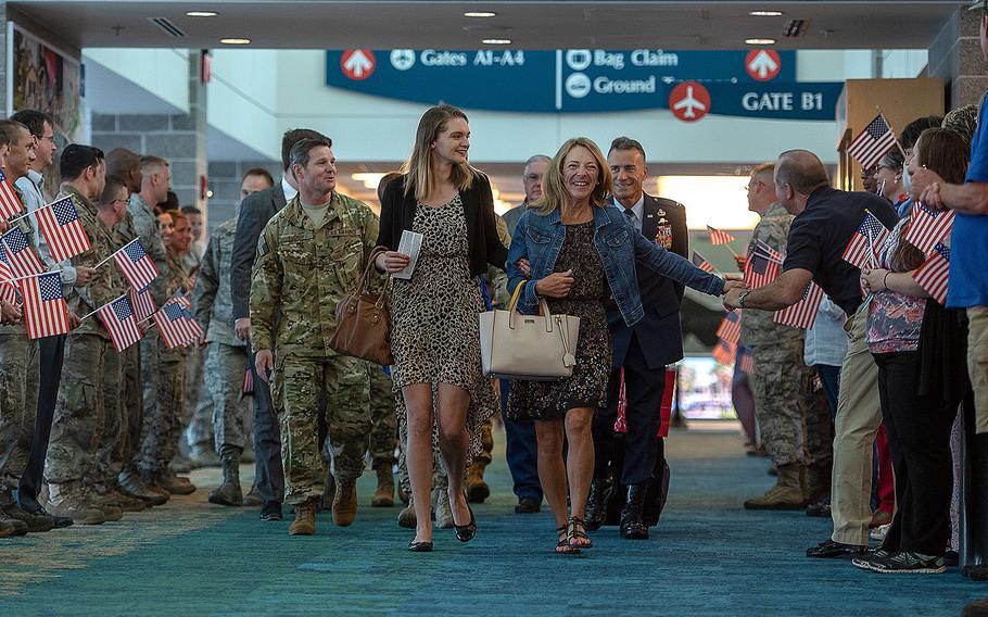 Valerie Nessel, right, the widow of U.S. Air Force Tech. Sgt. John Chapman, walks alongside her daughter Brianna, center, at Destin-Fort Walton Beach Airport, Florida on Aug. 20, 2018.