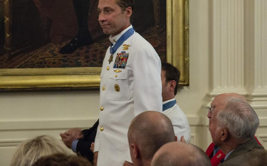 Medal of Honor recipient Master Chief Petty Officer Britt Slabinski stands as he's recognized by President Donald Trump during a ceremony at the White House, Aug. 22, 2018.