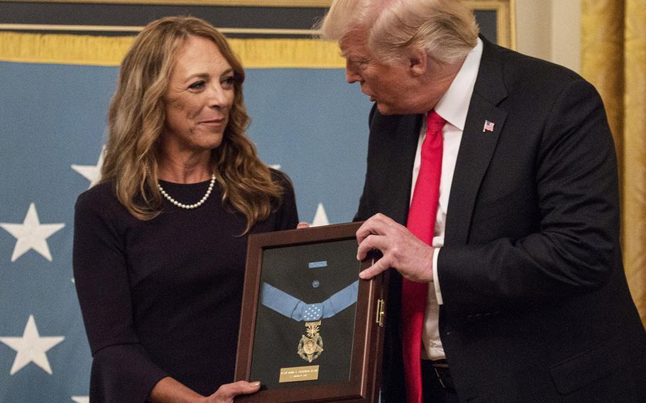 President Donald Trump presents Tech. Sgt. John A. Chapman's widow, Valerie Nessel, the Medal of Honor in a ceremony at the White House on Wednesday, Aug. 22, 2018.