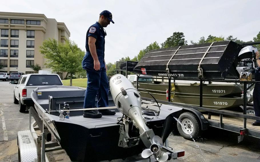 Petty Officer 1st Class Mike McHugh from the Coast Guard Gulf Strike Team checks the outboard engine of one of the Shallow Water Urban Search and Rescue boats staged in Augusta, Georgia, Sept. 13, 2018 in preparation for Hurricane Florence.