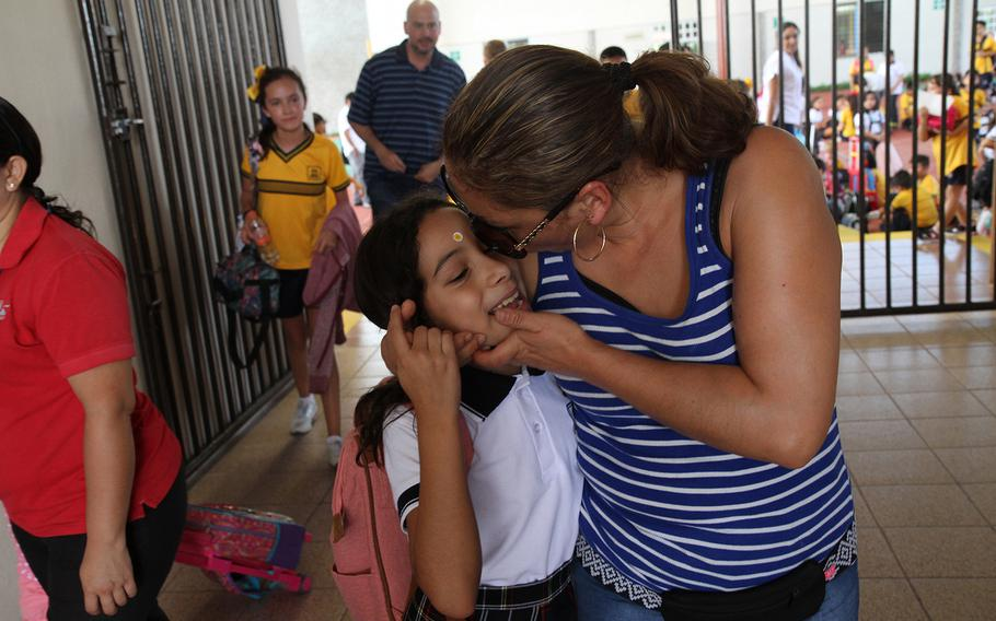 Alejandra Juarez, right, kisses her daughter Estela, 9, as she picks her up from her new school in Mexico's Yucatan on Aug. 30. Juarez was deported on Aug. 3, after 22 years in the U.S., where she built a home and family with her husband, an Iraq War veteran.