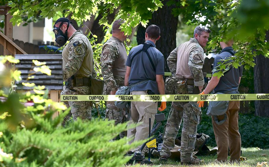 Law enforcement officers search a house on Wednesday, Oct. 3, 2018, in Logan, Utah. A man suspected of mailing suspicious letters to the Pentagon and President Donald Trump was taken into custody at the scene.