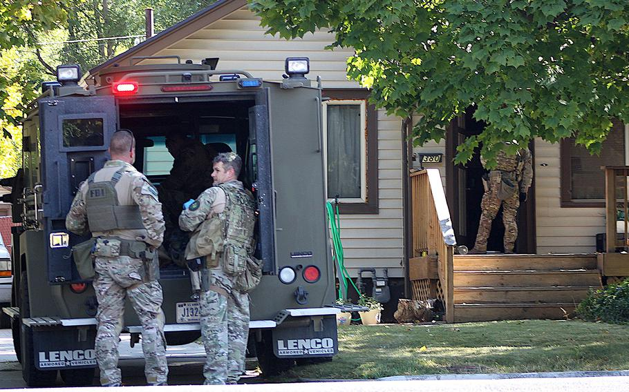 Law enforcement officers participate in an operation at a home in Logan, Utah on Wednesday, Oct. 3, 2018. A man suspected of mailing suspicious letters to the Pentagon and White House was taken into custody at the scene.