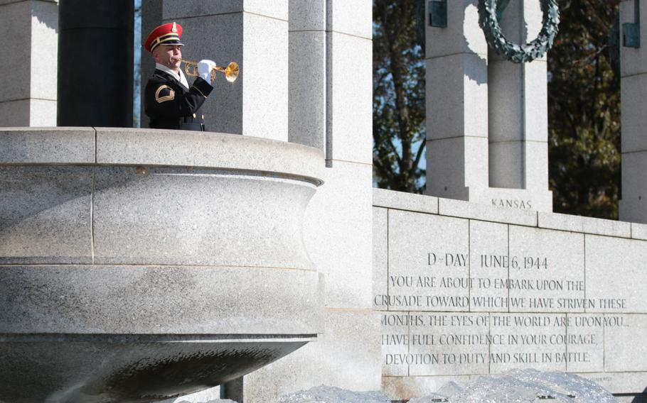 A soldier plays taps at a ceremony honoring World War II veterans at the National World War II Memorial in Washington, D.C., on Sunday, Nov. 11, 2018.