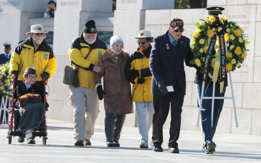 Volunteers help World War II veterans lay a wreath at a Veterans Day ceremony held at the National World War II Memorial in Washington, D.C., on Sunday, Nov. 11, 2018.