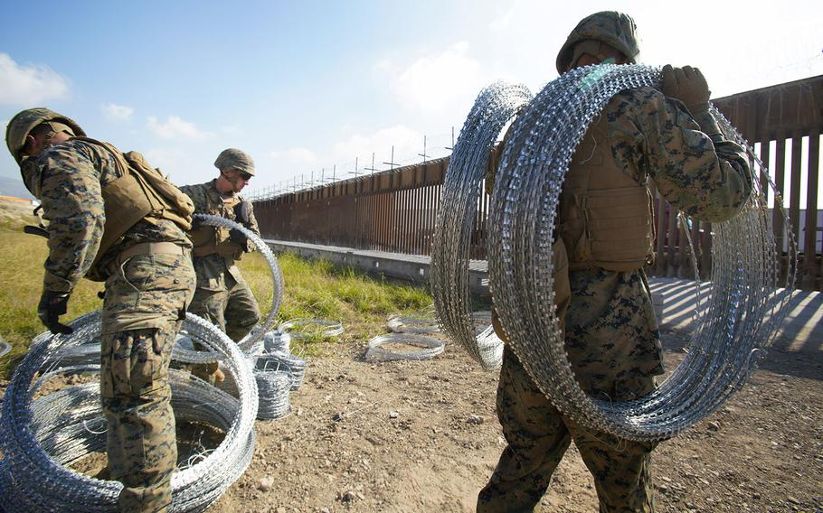 U.S. Marines deployed to the U.S. Mexico border in San Diego work to fortify the border wall with concertina wire at the Otay Mesa Port of entry.