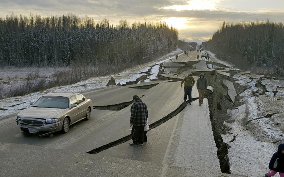 People walk along Vine Road after an earthquake on Friday, Nov. 30, 2018, in Wasilla, Alaska.