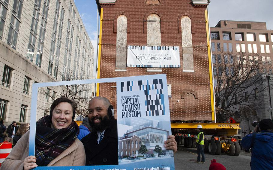 Spectators pose for a photo as Washington's oldest synagogue building is moved down 3rd St. Northwest to its permanent location at the Lillian and Albert Small Jewish Museum site on January 9, 2019.