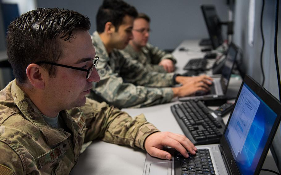"""Staff Sgt. Roger Murvin troubleshoots a computer at the hub at Barksdale Air Force Base, La., Dec. 11, 2018.  Four congressmen are urging the FBI to investigate """"foreign entities"""" believed to be targeting servicemembers and veterans online with false information."""