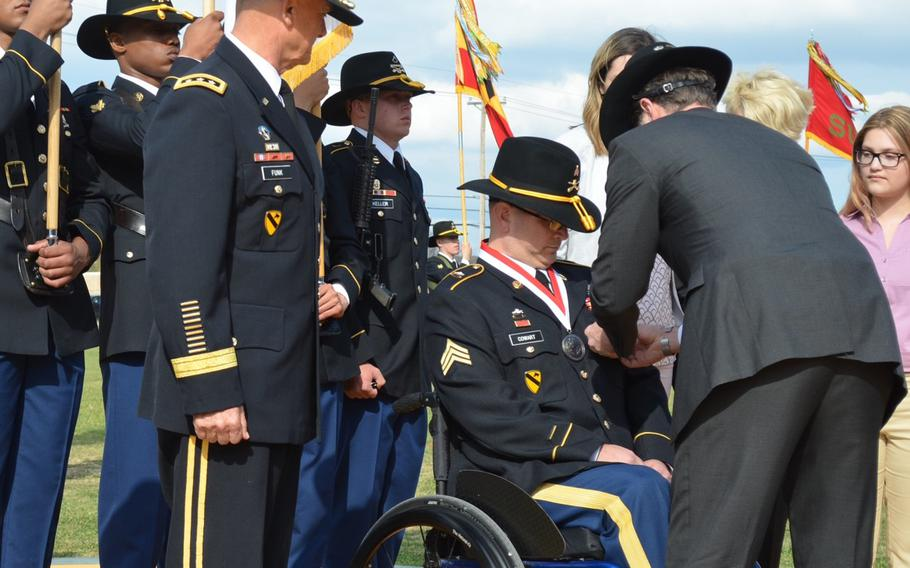 Chris Widell pins the Distinguished Service Cross on retired Sgt. Daniel Cowart during a ceremony March 20 at Fort Hood, Texas. Widell is a former Army officer and friend who Cowart said helped him regain confidence and purpose after being wounded in combat. Cowart received an upgrade from the Silver Star medal after a review of his actions on May 13, 2007, in Samarra, Iraq.