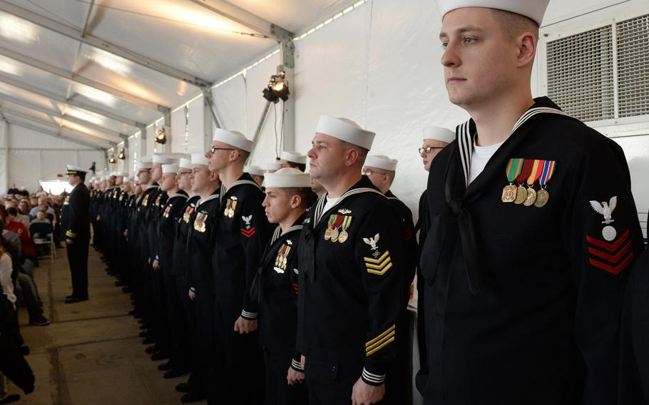 Sailors wearing red or  yellow stripes stand in formation during the commissioning ceremony of the USS South Dakota on Feb. 2, 2019.
