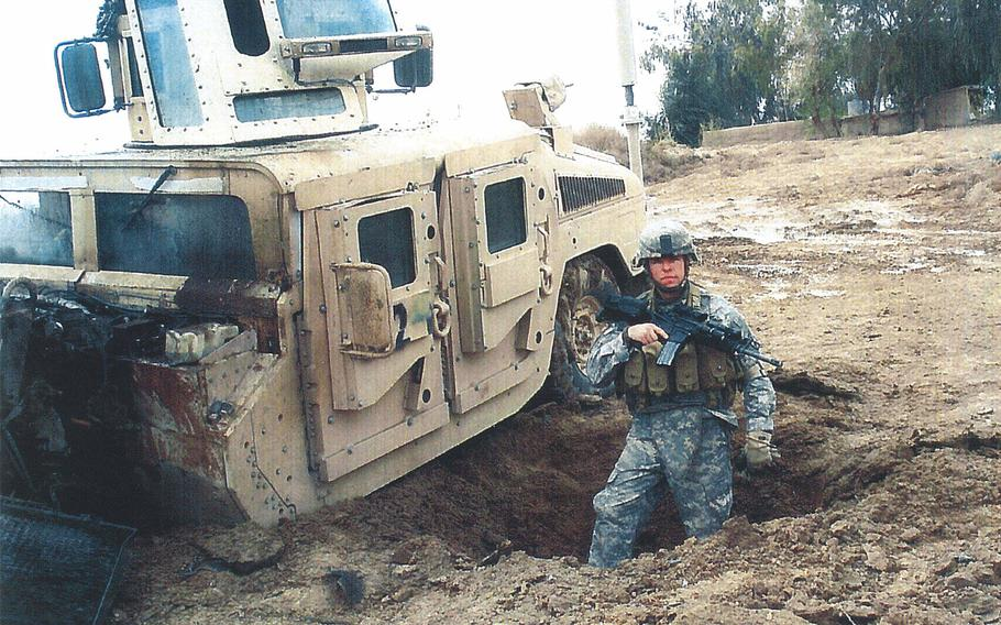 Staff Sgt. Travis Atkins stands in the crater from an improvised-bomb attack that he survived in Iraq.