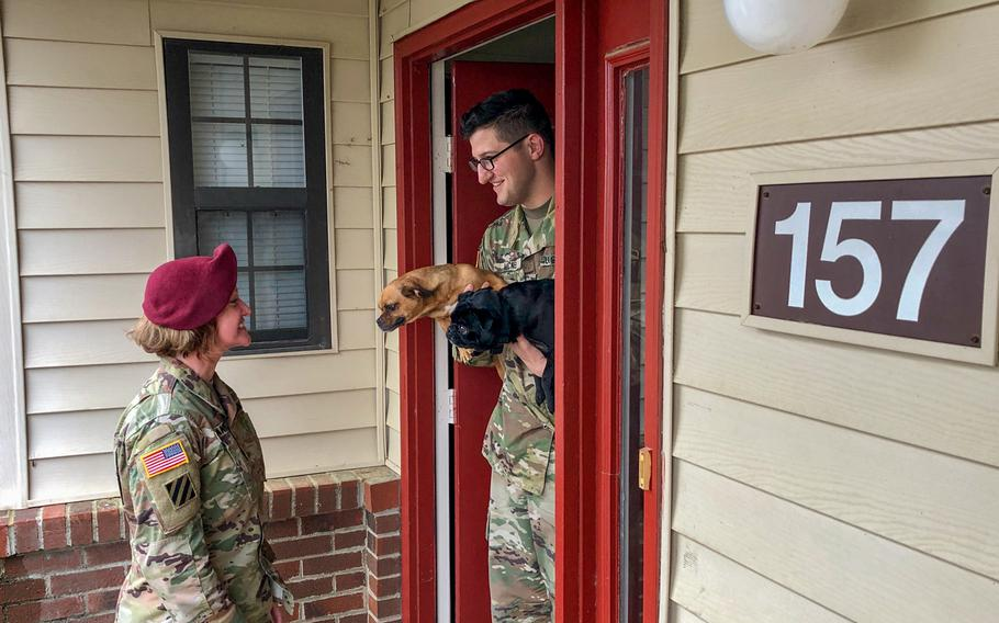 Sgt. Andrew McNeil (right), a public affairs mass communication noncommissioned officer, greets Maj. Tabitha Hernandez, commander, 22nd Mobile Public Affairs Detachment, Headquarters and Headquarters Battalion, XVIII Airborne Corps, at his door with his dogs prior to a command visit at Fort Bragg, N.C., April 5, 2019. L