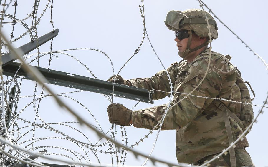 A soldier from the 161st Engineer Support Company (Airborne) secures concertina wire to the existing border fence near the World Trade International Bridge in Laredo, Texas, April 11, 2019.