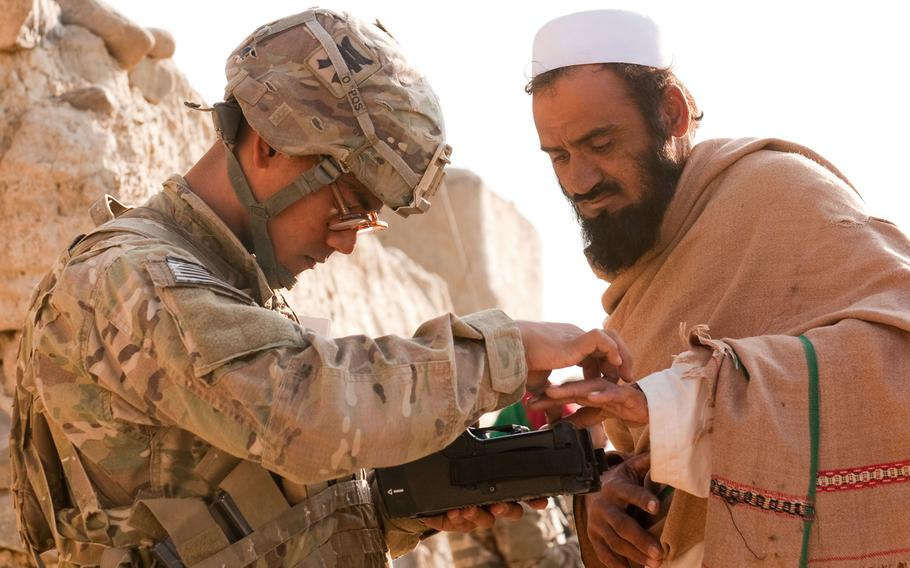 U.S. Army Pfc. Mark Domingo, left, takes an Afghan man's fingerprints in the village of Dande Fariqan, in Afghanistan's Khowst province on Nov. 5, 2012. Domingo, who converted to Islam and discussed launching various terror attacks throughout Southern California, was arrested as he plotted to bomb a white supremacist rally, federal prosecutors said Monday, April 29, 2019.