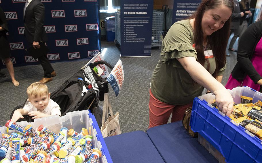 A boy watches as Mom prepares a snack package for U.S. servicemembers during a USO event at the Dirksen Senate Office Building on Capitol Hill, April 30, 2019.
