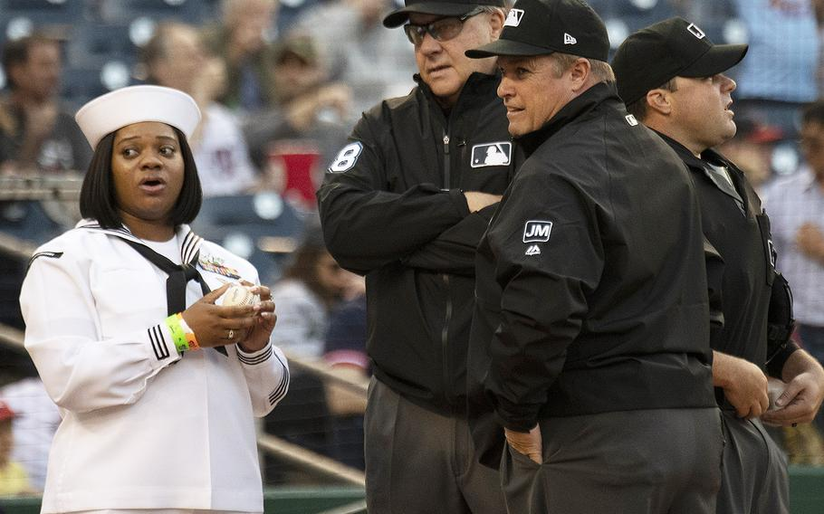 Yeoman 1st Class Whitney Sisson stands with hte umpires as she prepares to present the game ball to Washington Nationals catcher Yan Gomez during Navy Night ceremonies at Nationals Park in Washington, D.C., May 1, 2019.