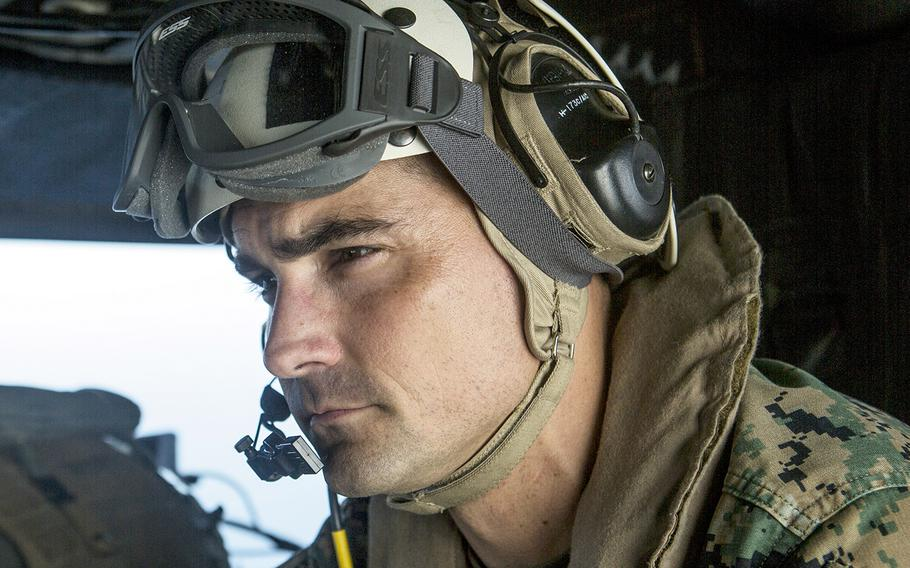 In a Nov. 17, 2018 file photo, U.S. Marine Corps Lt. Col. Francisco Zavala, commanding officer of Special Purpose Marine Air-Ground Task Force-Peru, looks out over the Pacific Ocean as he flies in a UH-1Y Venom